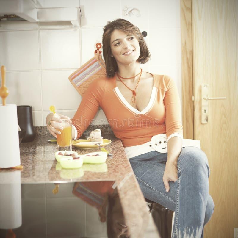 Kvinna som äter hennes frukost royaltyfri foto
