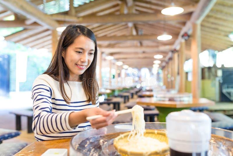 Kvinna som äter japanska somen i restaurang arkivfoton