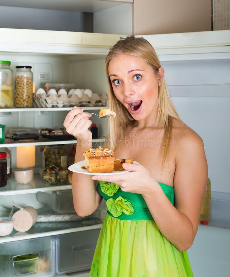 Kvinna som äter kakan från kylen royaltyfri bild