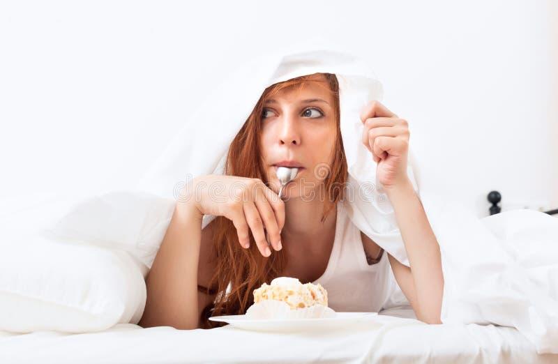 Kvinna som äter kakan under arket royaltyfri bild