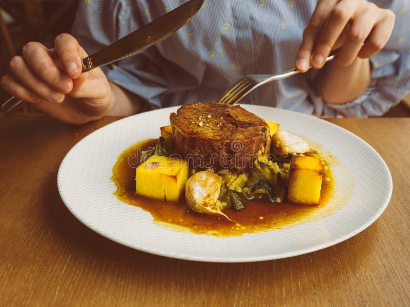 Kvinna som äter läckert kött med polent arkivfoton