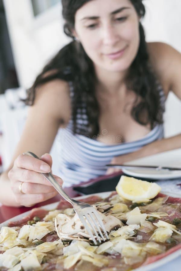Kvinna som äter nötköttcarpaccio i intalian restaurang royaltyfri bild
