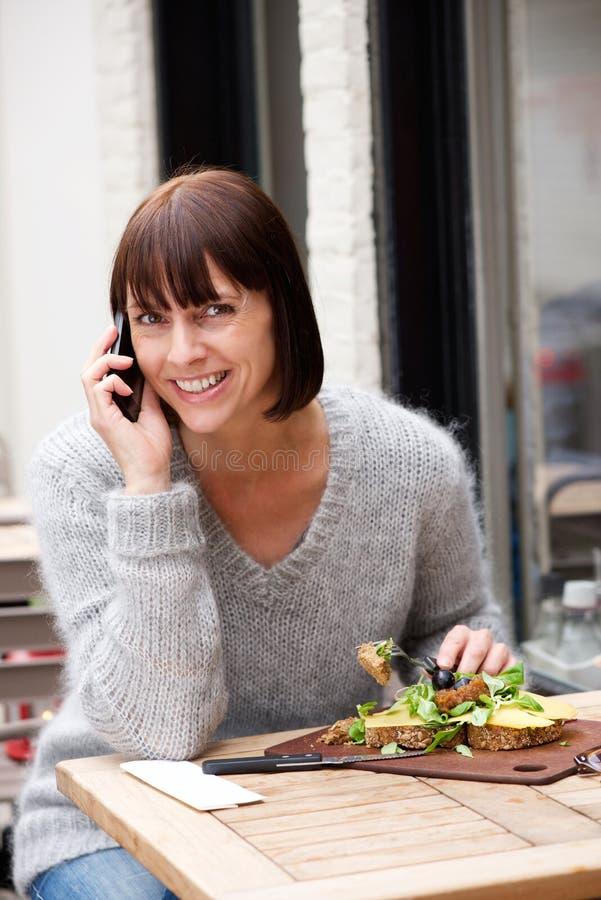 Kvinna som äter och ler med mobiltelefonen royaltyfria bilder