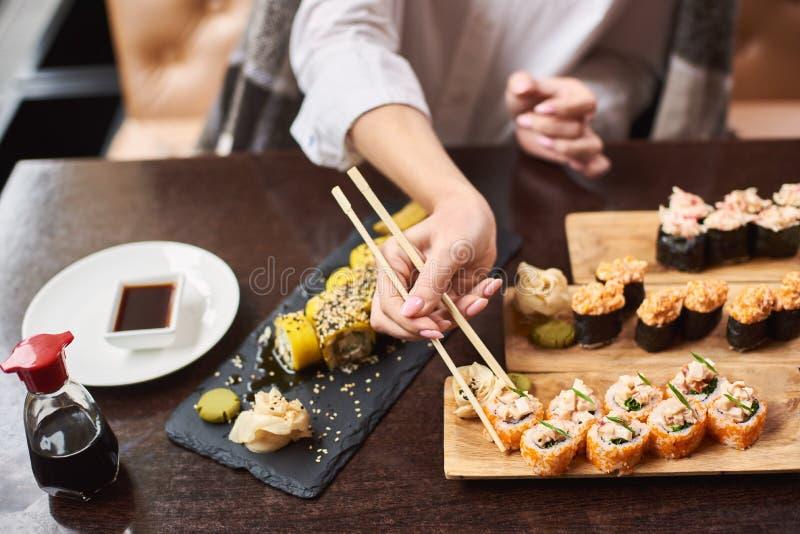 Kvinna som äter och tycker om den nya sushi i lyxig restaurang royaltyfria bilder