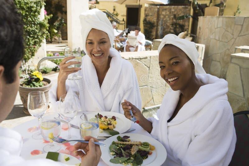 Kvinna som äter organiskt mål med vänner fotografering för bildbyråer