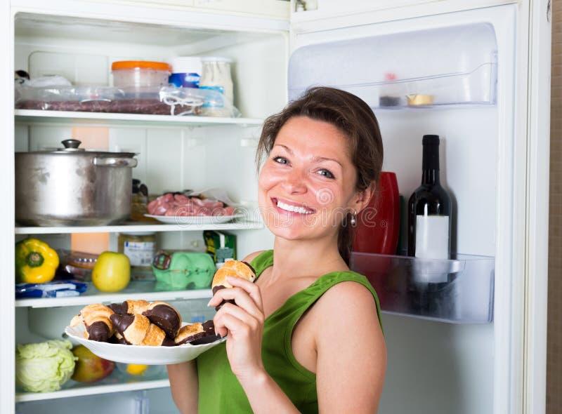 Kvinna som äter pannkakan nära kylskåpet arkivfoton