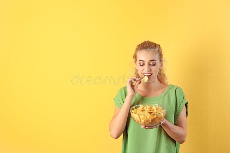 Kvinna som äter potatischiper på färgbakgrund arkivbild