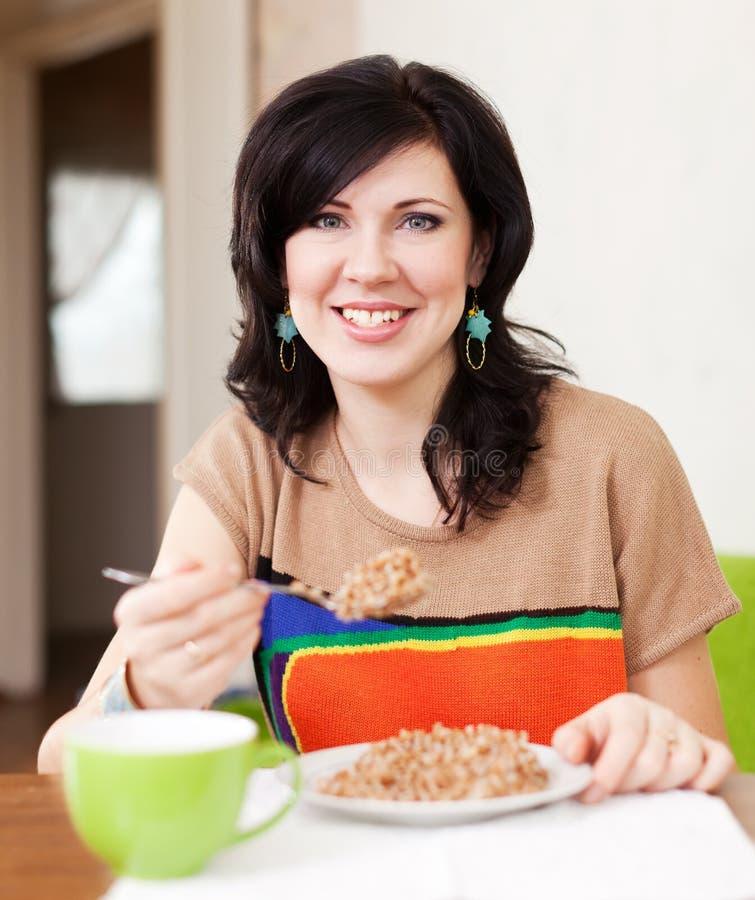 Kvinna som äter sädes- hemmastatt royaltyfri fotografi