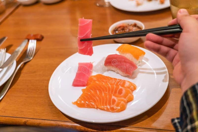 Kvinna som äter sashimien med pinnar royaltyfri foto