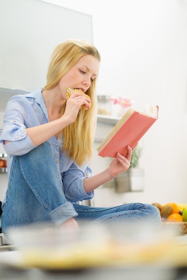Kvinna som äter smörgåsen och läseboken i kök royaltyfria bilder
