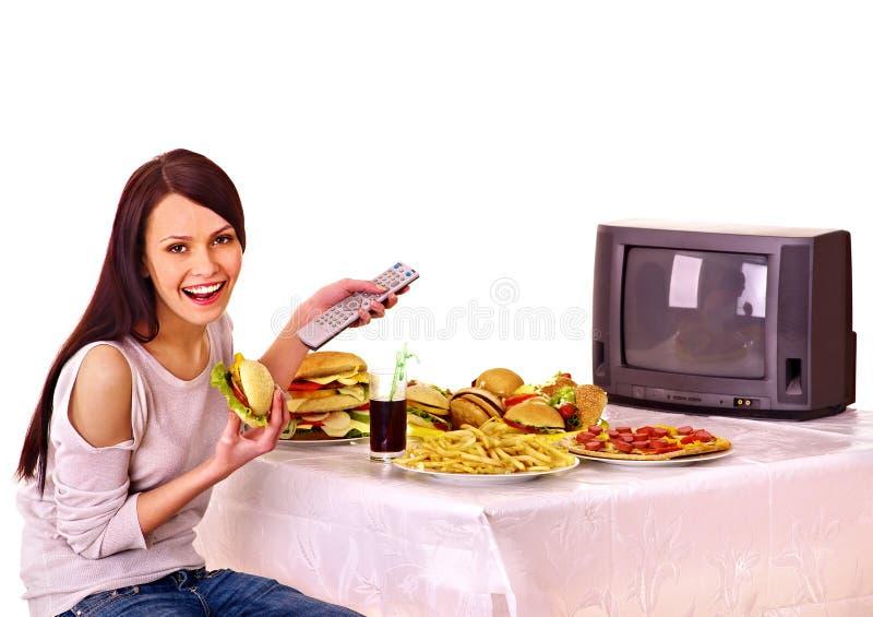 Kvinna som äter snabbmat- och hålla ögonen påTV. royaltyfria bilder