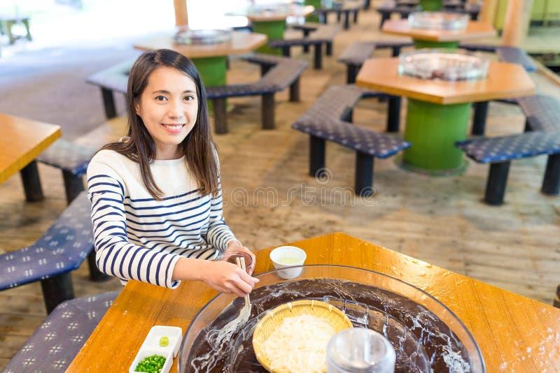 Kvinna som äter somen i japansk restaurang royaltyfri bild