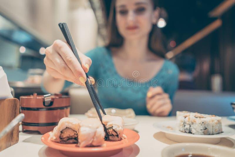 Kvinna som äter sushimat i japansk restaurang arkivbild