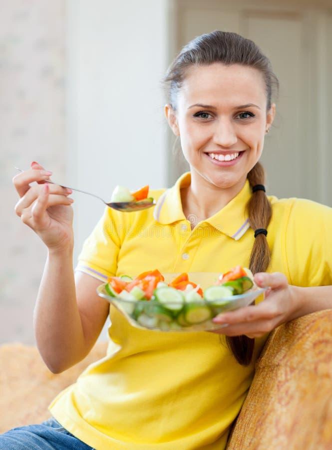 Kvinna som äter veggiesallad på soffan arkivbilder