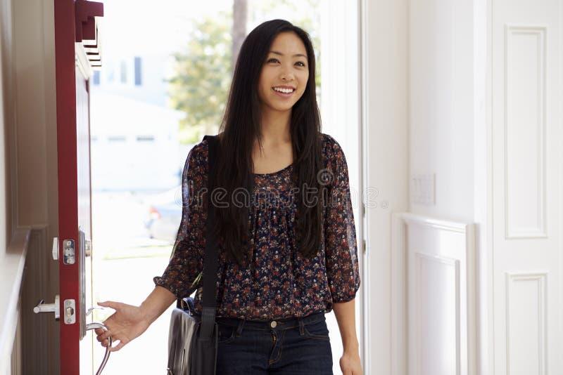 Kvinna som öppnar den Front Door Of Home After dagen på arbete royaltyfria foton