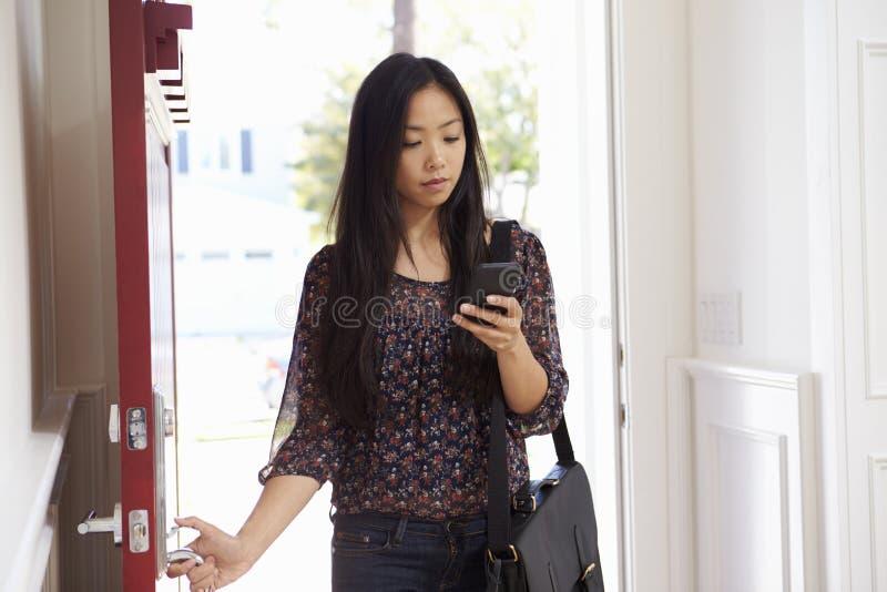 Kvinna som öppnar den Front Door Whilst Checking Mobile telefonen royaltyfria foton