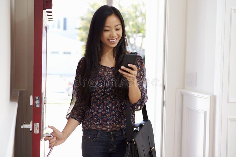 Kvinna som öppnar den Front Door Whilst Checking Mobile telefonen arkivbild