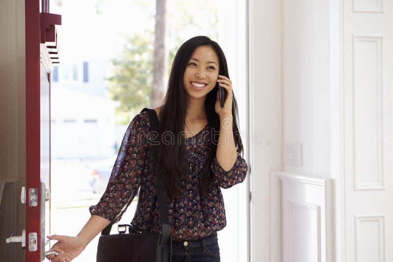 Kvinna som öppnar den Front Door Whilst Talking On mobiltelefonen arkivbild