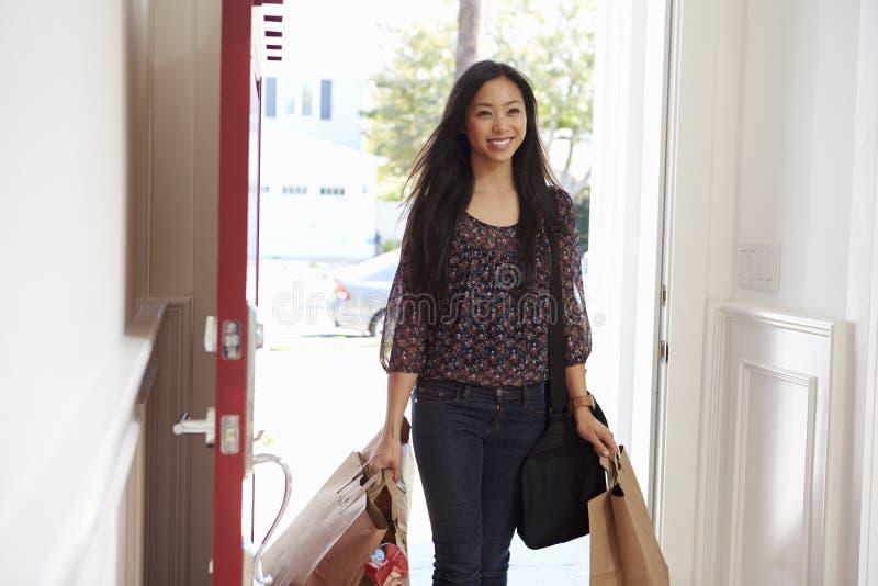 Kvinna som öppnar Front Door Of Home Carrying livsmedelsbutikpåsar royaltyfria foton