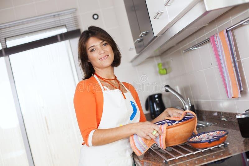 Kvinna som öppnar kökugnen royaltyfria foton