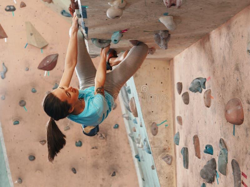 Kvinna som öva i klättringidrottshall royaltyfria foton
