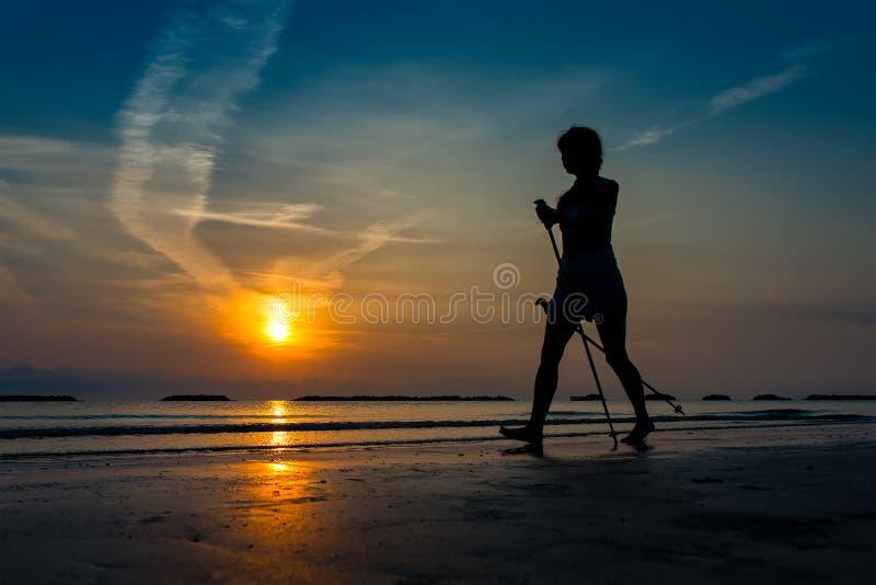 Kvinna som öva nordiskt gå i stranden på soluppgång in sent royaltyfri fotografi