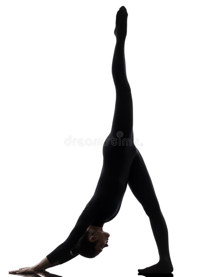 Kvinna som övar gymnastisk yoga   Adho Mukha Svanasana silhouett arkivbilder