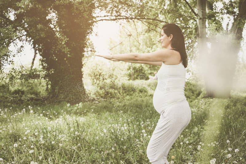Kvinna som övar i utomhus- Ung kvinna i äng royaltyfri bild