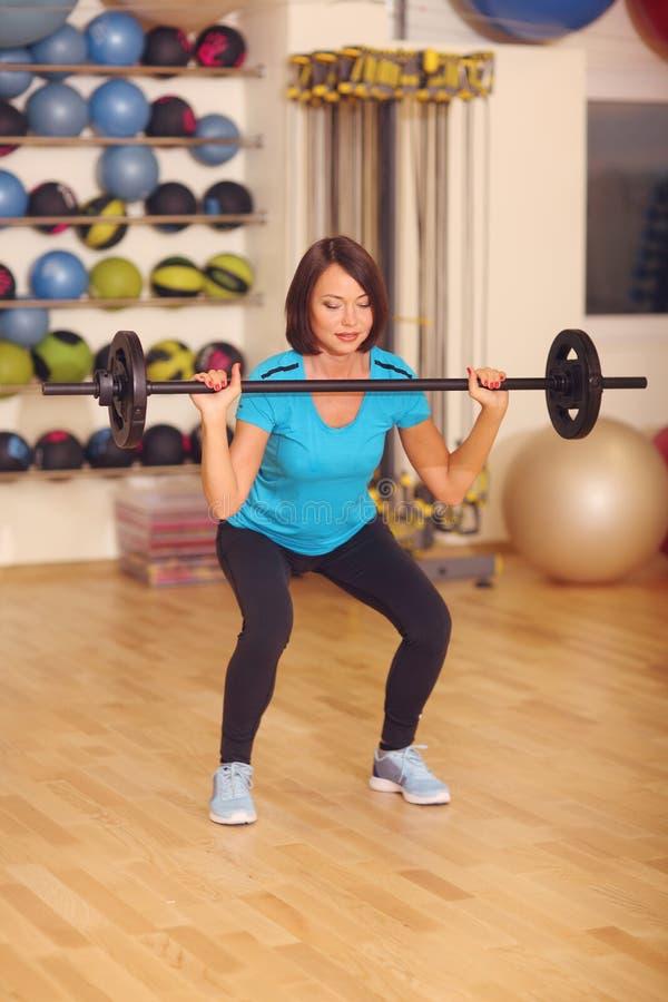 _ kvinna som övar med skivstången i konditiongrupp Kvinnlig genomkörare i idrottshallen som gör squats med vikt arkivbild