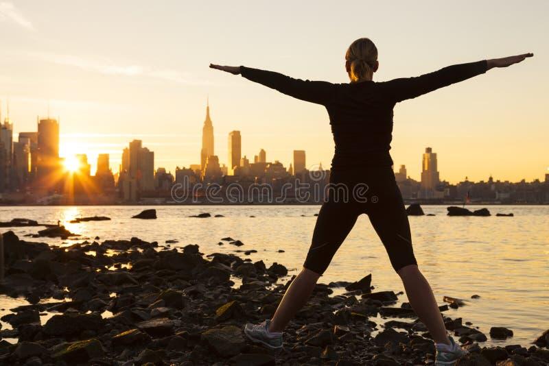 Kvinna som övar på soluppgångNew York City horisont royaltyfria foton