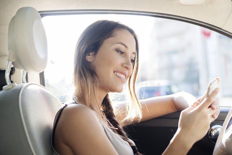 Kvinna som överför ett meddelande med hennes mobiltelefonsammanträde i hennes bil royaltyfri foto