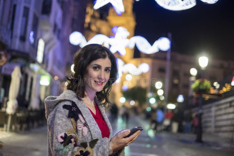 Kvinna som överför och ser sociala nätverksmeddelanden i vinterchri arkivfoto