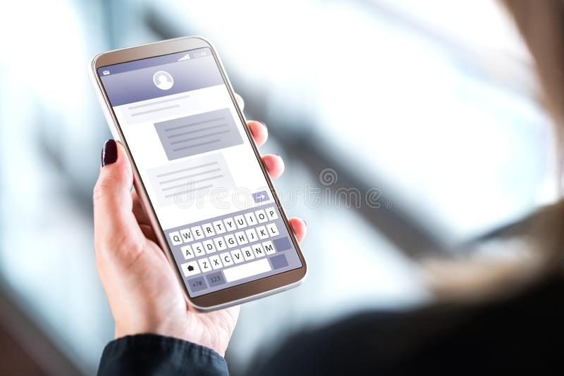 Kvinna som överför textmeddelanden med mobiltelefonen arkivfoton