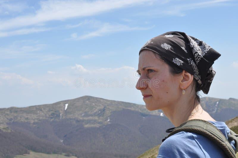 Kvinna som överst vilar av ett berg Fotvandra och klättra på slingan royaltyfria foton