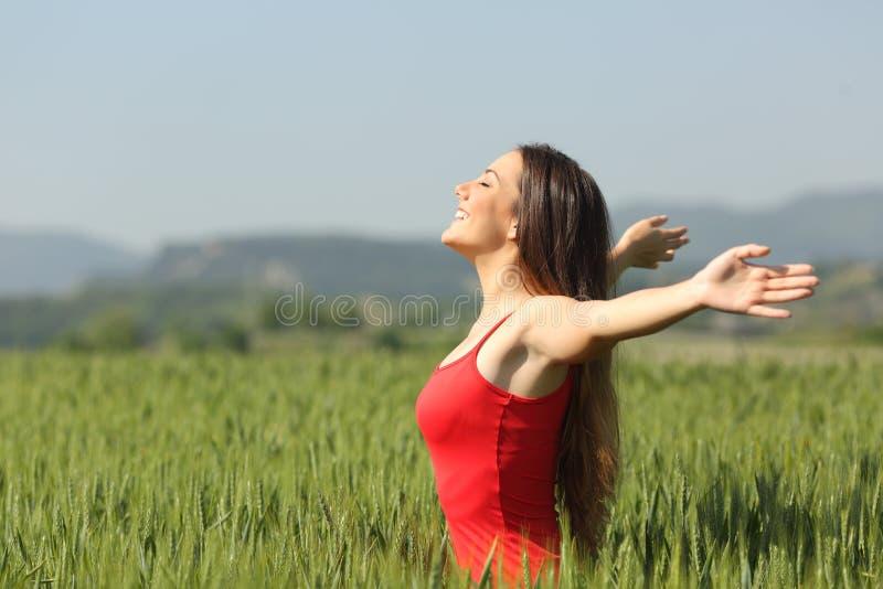 Kvinna som andas djup ny luft i ett fält arkivbilder