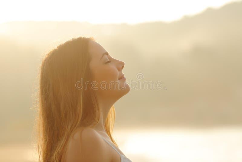Kvinna som andas djup ny luft i morgonsoluppgången royaltyfri fotografi
