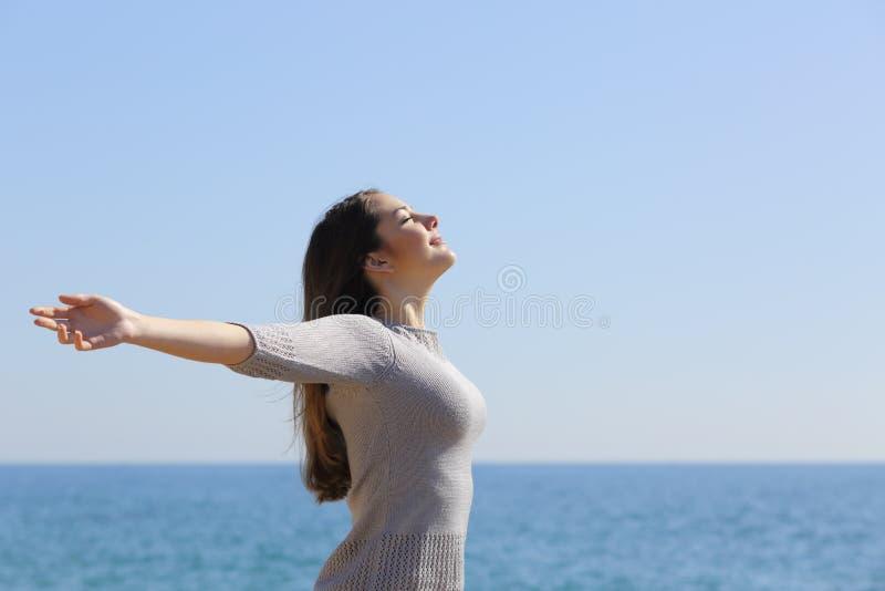 Kvinna som andas djup ny luft och lyfter armar arkivfoto