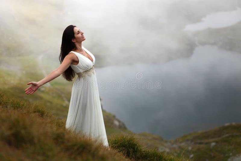 Kvinna som andas ny bergluft arkivbild