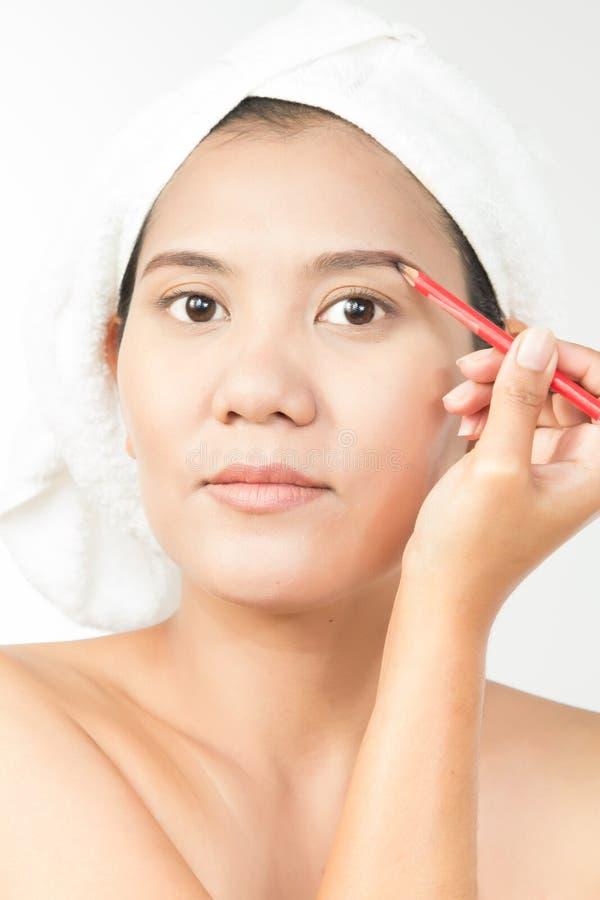 Kvinna som använder ögonbrynblyertspennan royaltyfria foton