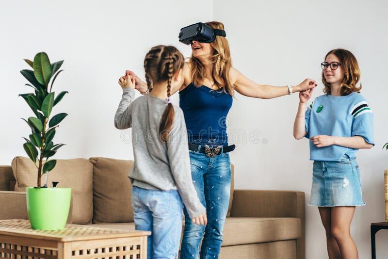 Kvinna som använder anseende för virtuell verklighet för VR-hörlurar med mikrofonexponeringsglas hemmastatt på vardagsrum med ung fotografering för bildbyråer
