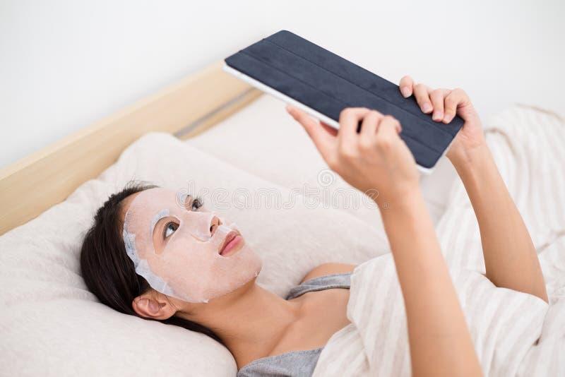 Kvinna som använder ansikts- maskerings- och minnestavlaPC royaltyfria foton