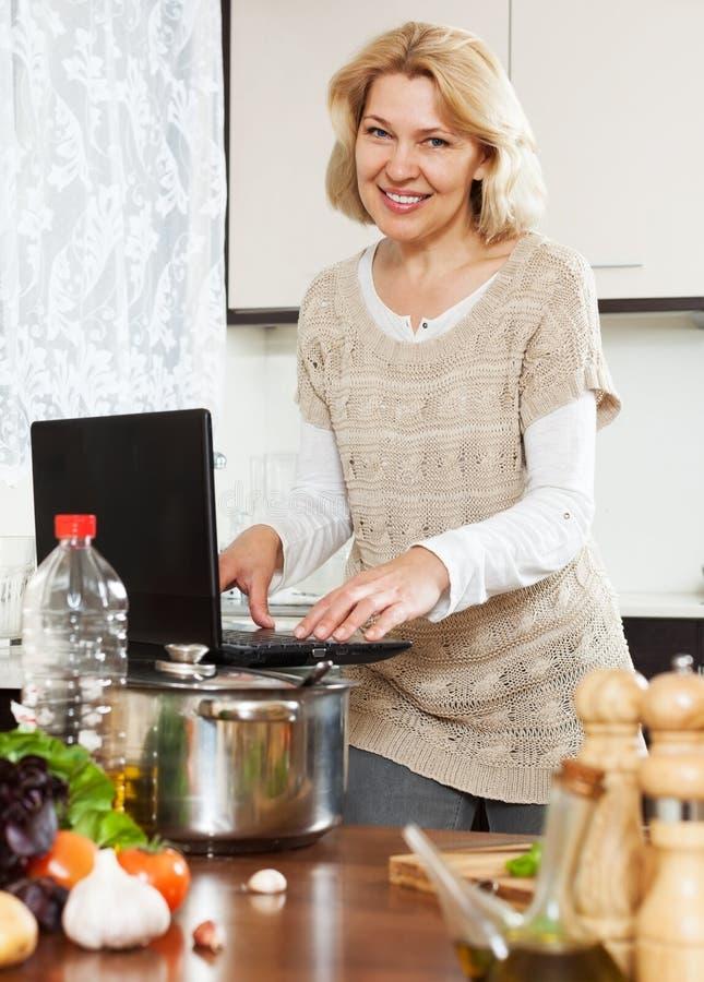 Kvinna som använder anteckningsboken, medan laga mat soppa arkivbild