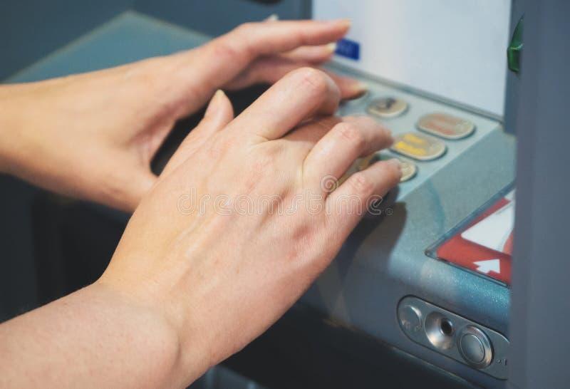 Kvinna som använder ATM på gatan royaltyfria foton
