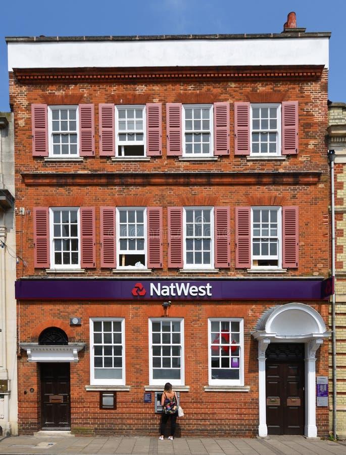 Kvinna som använder ATM på Natwest bankSt Ives Cambridgeshire England royaltyfria bilder