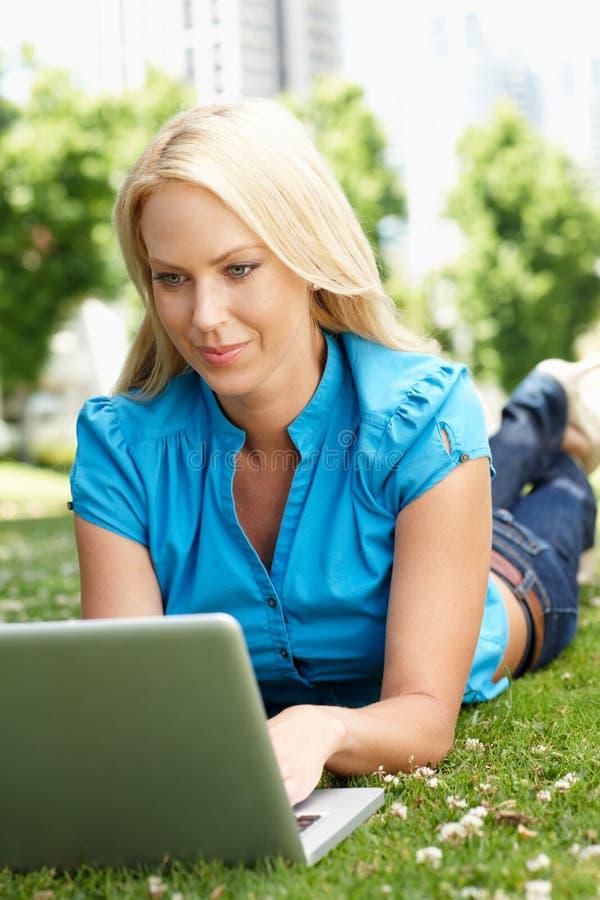 Kvinna som använder bärbar dator i stadspark royaltyfri foto
