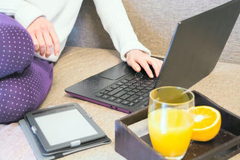 Kvinna som använder bärbar dator- och drinkfruktsaft, inomhus arkivbild