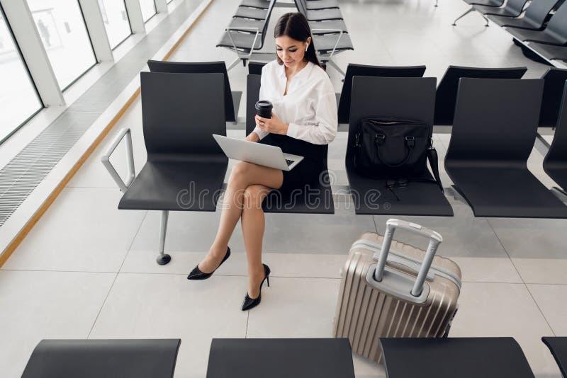 Kvinna som använder bärbar datordatoren på flygplatsterminalen som sitter med bagageresväskan för väntande flyg för affärslopp royaltyfria foton
