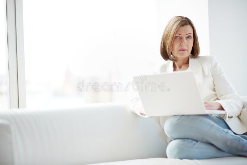 Kvinna som använder bärbara datorn arkivfoton