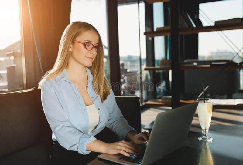 Kvinna som använder bärbara datorn i coffee shop royaltyfria bilder