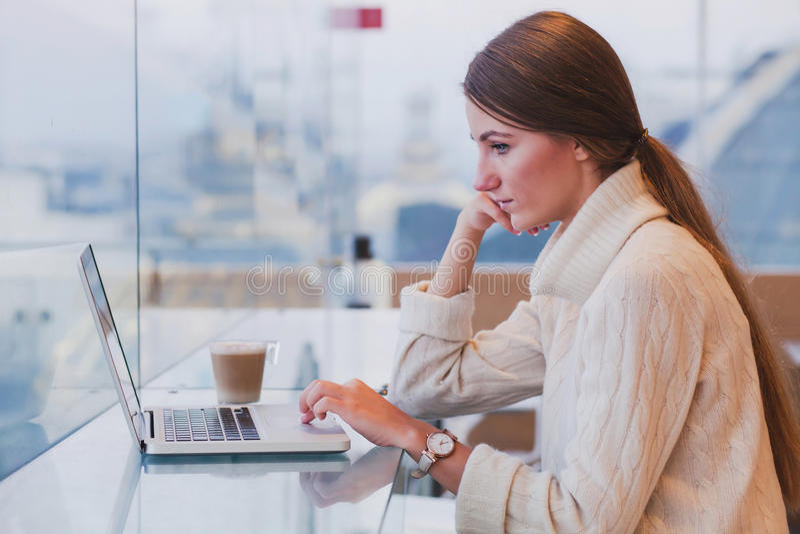 Kvinna som använder bärbara datorn i modern kaféinre royaltyfria foton